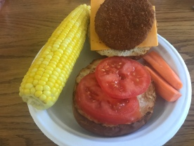 Ta-da! Quick meal. I put my onions on the bottom, then tomato, cheese on the other side and my chik patty. One ear of corn and some fresh peeled raw carrots to make a full meal!!